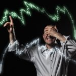 scared trader pointing to stock market charts with eyes closed