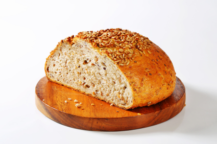 sliced fresh bread loaf with sunflower and sesame seeds on a round wooden cutting board
